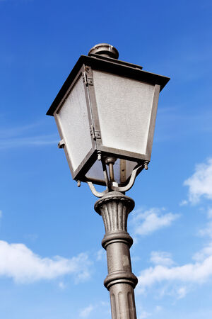 lampost: Detail of an old lampost on a blue sky with clouds  Stock Photo