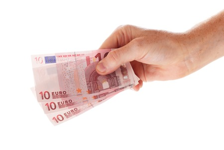 A hand holding three ten euro bills, isolated on white background. photo