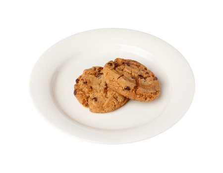 small plate: Two chocolate chip cookies on a white small plate isolated on white bakground.