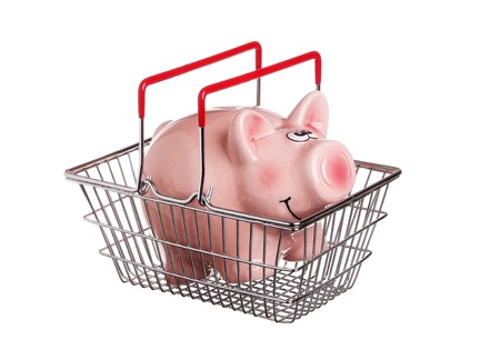 One piggy bank in a shopping basket with red handles, isolated on white. Stock Photo