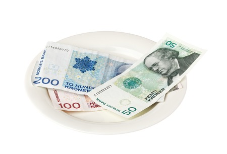 small plate: Norwegian banknotes on a small plate isolated on white background.