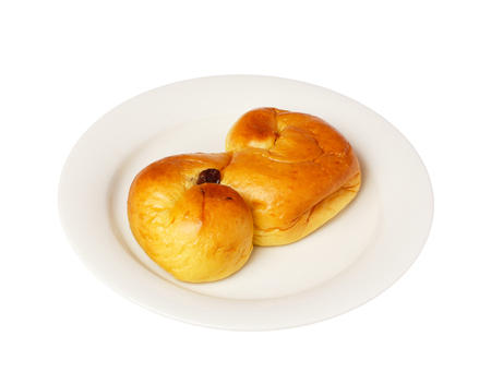 in conjunction: Typical Swedish saffron bun \lussekatt\ eaten in conjunction with the Lucia celebrations and Christmas celebrations served on a small white plate..