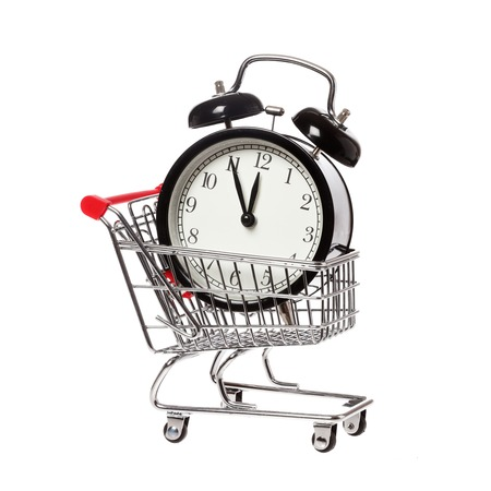 A shopping cart with an alarm clock that shows eleven fifty-five isolataed on white background. photo