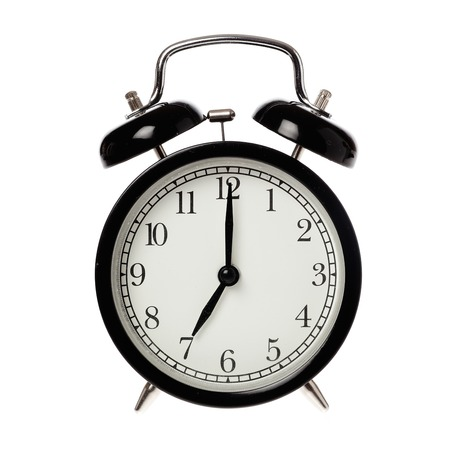 Black alarm clock with analog display seven o clock isolated on white. Stock Photo