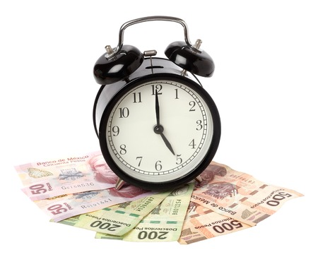 pesos: One black alaram clock on Mexican Pesos banknotes isolated on white.