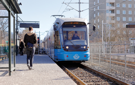 electric tram: Stockholm, Sweden- March 8, 2015: An electric blue Stockholm public transport suburban tram arriving at the stop Valla torg with passangers waiting.