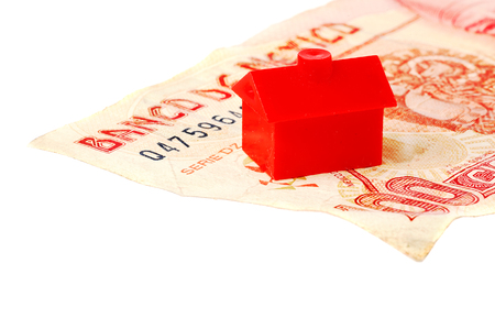 house prices: A red litle plastic house on a Mexican one hundred Pesos banknote isolated on white.