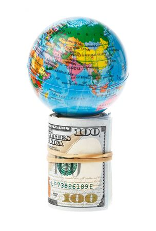 supported: The world supported by a roll of US 100 Dollars bills, isolated on white.