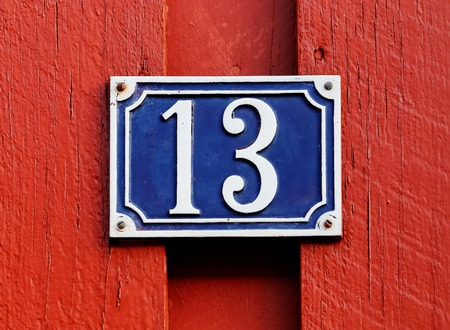 Number thirteen sign on a red wooden wall.