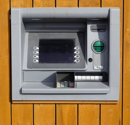 A ATM mounted in a yellow wooden wall.