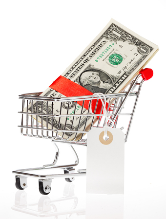 business metaphore: US Dollars wrapped with a red satin ribbon with an attached price tag in a shoping cart isolated on whitebackground. Stock Photo