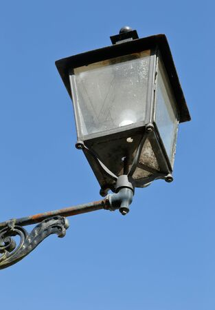 source of iron: Old fashioned lamp against blue sky. Stock Photo