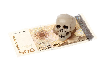 Norwegian 500 kroner bill with a small plastic scull isolated on white background. Stock Photo
