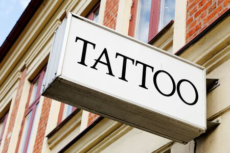 Exterior sign at a tattoo studio. Stock Photo