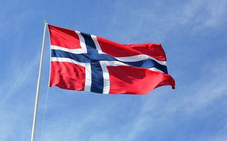 Norwegian flag against blue sky.