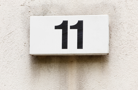 Number eleven on a white plate attached to a buildings exterior wall.