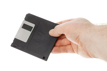 35: One human hand holding a black 3.5 inch manetic diskette isolated on white.