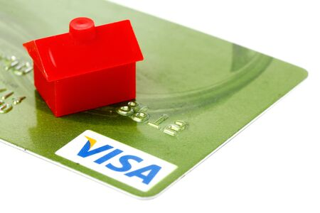 visa credit card: One litle red house on green VISA credit card isolated on white background. Editorial