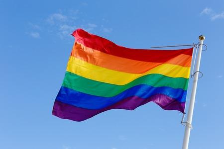 Close-up van een regenboog vlag op de blauwe hemel.