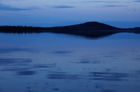 stillness: Stillness of twilight in northern Sweden with river in the foreground. Stock Photo