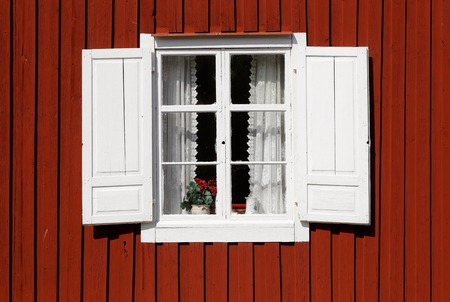 Red painted wooden wall of the house with closed  windows that have opened white shutters. Stock Photo