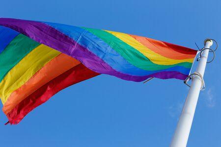rainbow flag: Close-up of a rainbow flag on blue sky. Stock Photo