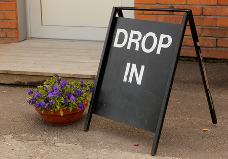 A  Drop in sign with white text onblack outside a building.