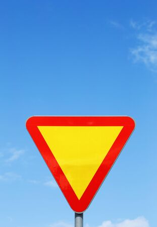 give the way: Swedish traffic sign Give Way on blue sky. Stock Photo