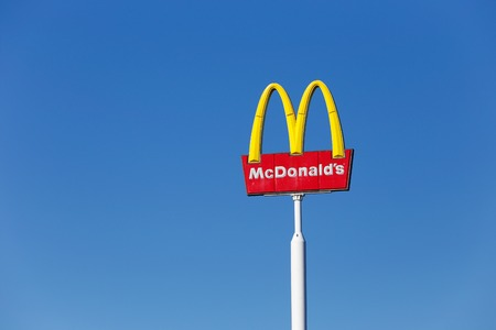 McDonalds yellow and red logo advertising sign placed on a pole with a clear blue sky Editorial