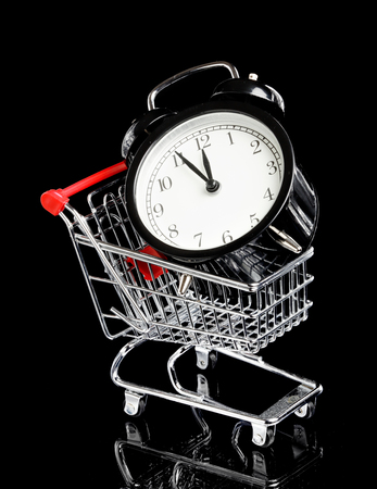 five to twelve: An black alarm clock in a small shopping trolley display time is five to twelve isolated on black. Stock Photo