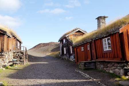 slag: Old wooden buildings with thatched roofs adjacent to the slag heap in the mining town of Roros in Norway. Stock Photo