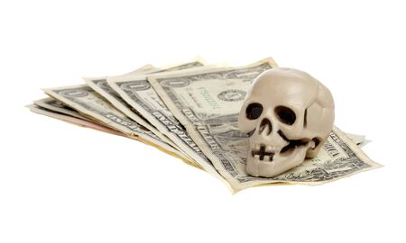 litle: A small plastic skull on money faned out on white background.