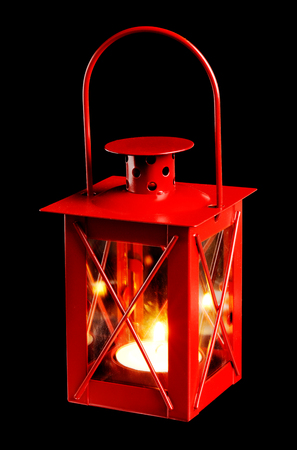 lighted: A small red lantern with a lighted candle isolated on black background. Stock Photo