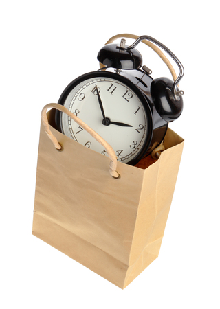 buying time: One black alarm clock inside a brown paper bagwith handles isolated on white.