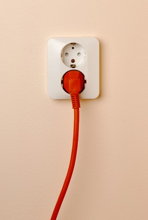 inserted: Wall mounted outlet with a red power plug inserted.