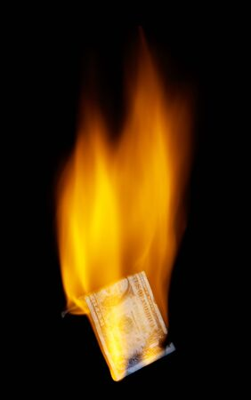 burning money: One dollar banknote in flames on black. Stock Photo