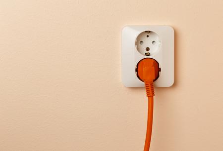 Een oranje gekleurde stekker met snoer aangesloten op een stopcontact dat veel voorkomt in Europa.