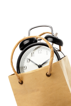buying time: Cllose-ip of one black alarm clock inside a brown paper bagwith handles isolated on white. Stock Photo