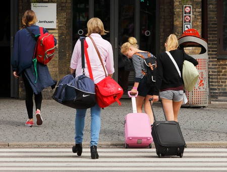 gothenburg: Gothenburg, Sweden - July 1, 2014: Four people with bags on their way to the railway station Centralstationen in Gothenburg.