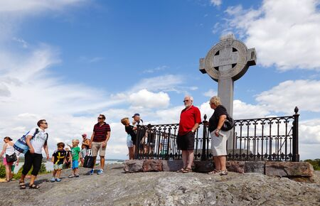 celtic cross: Bjorko - Sweden - July 19, 2014:People at Ansgar monument in the shape of a Celtic cross as the 1000 anniversary of the missionary Ansgars arrival at Birka erected the cross in 1834 on Bjorko island, Sweden.