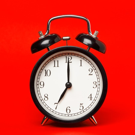 red background: Alaram clock on red displaying seven o clock.