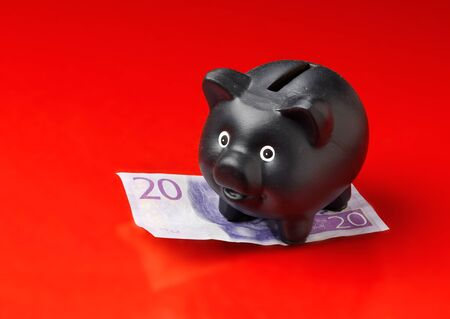 Black piggy bank on a Swedish twenty krona banknote ioslated on red background. Stock Photo