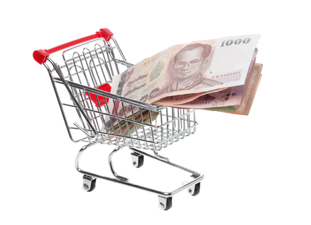 shoppingcart: Shoppingcart filled with Tahi baht banknotes, isolatedon white. Stock Photo