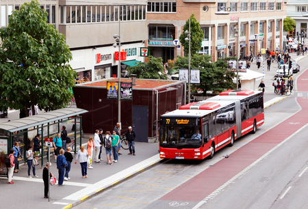 urban city: Stockholm, Sweden - August 31, 2015: Red bus in traffic for SL traffic on line 77 with the destination Karolinska Hospital arrives to stop Hornstull at the street Langholmsgatan where people are waiting.