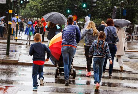Stockholm, Zweden - 29 juli 2015: Regen op een zebrapad op straat Hamngatan, waar een vrouw met een kinderwagen heeft een regenboog patroon paraplu.