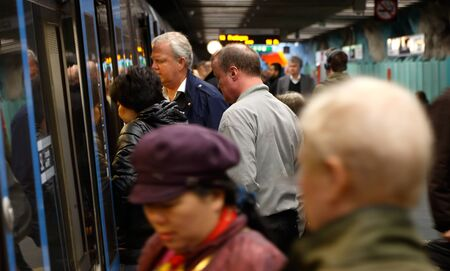 many doors: Stockholm, Sweden - April 29, 2014: Rush hour at the subway station Stadion with passengers boarding a subway train.