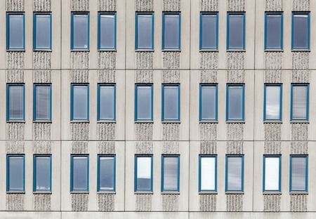 grooved: Elongated narrow windows in three rows of grooved concrete facade.