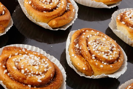 baking tray: Close-up of baked cinnamon buns in tins of graeseproof paper on a baking tray.