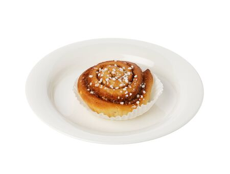small plate: Cinnamon bun on a small plate isolated on white.