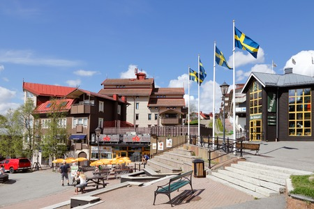 flagpoles: Are, Sweden - May 30, 2016: The square in Åre with three flagpoles with Swedish flags hoisted. Some people sit at the Max hamburger restaurants outdoor dining area.